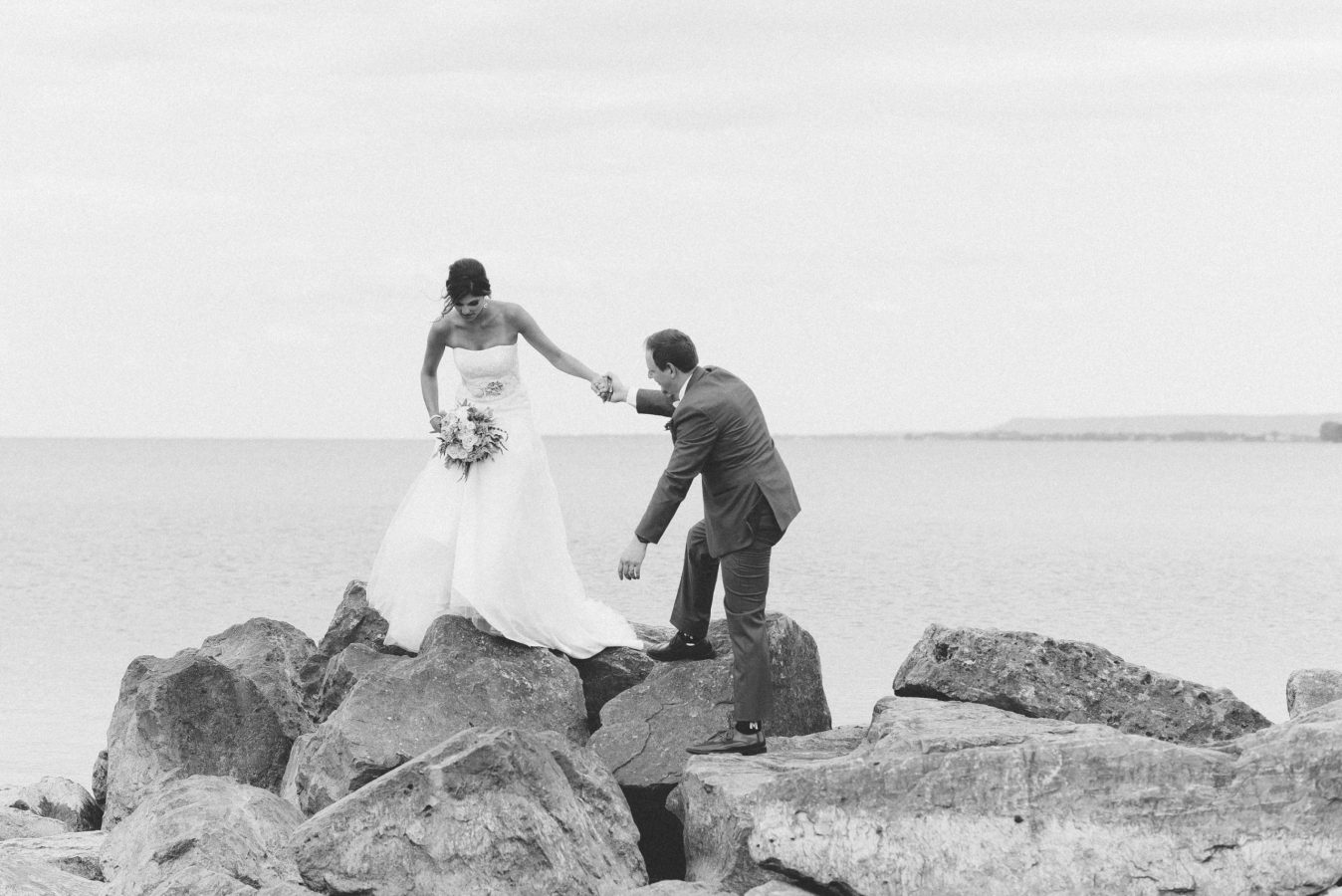 groom helps bride down from rocks at lakeview burlington wedding