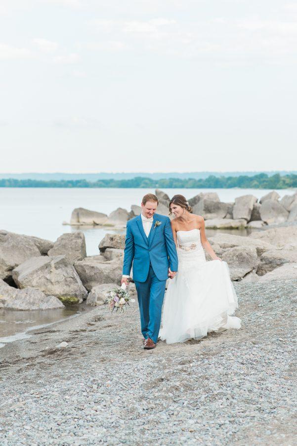 bride and groom walk along beach at lakeview burlington