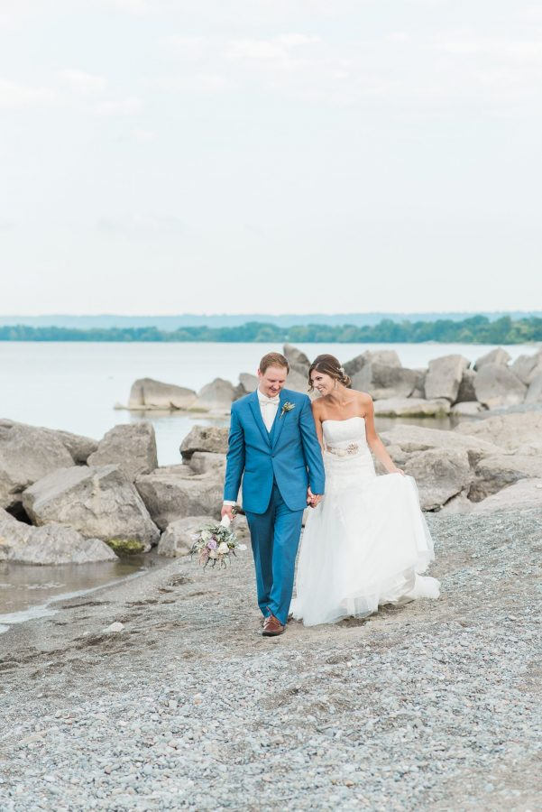 bride and groom walk along beach at lakeview burlington