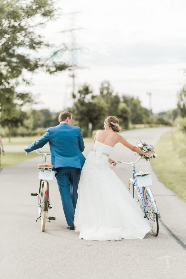 bride and groom walk with vintage bikes at lakeview burlington