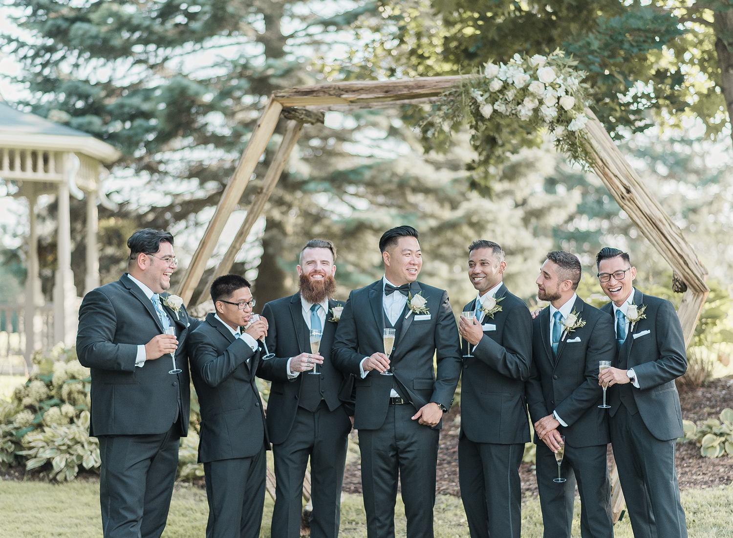 groom and groomsmen drinking champagne