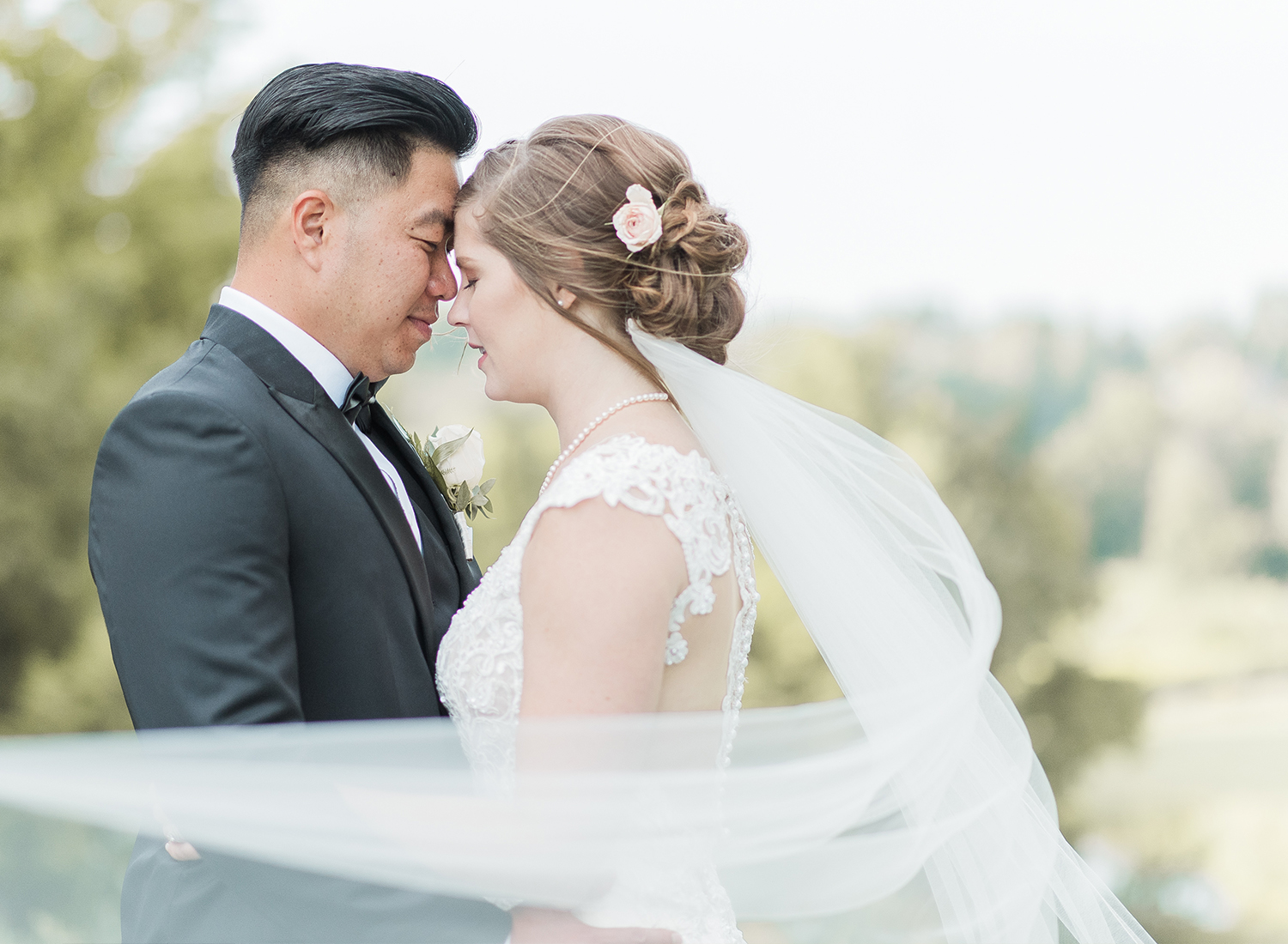 bride and groom posing with veil blowing in wind