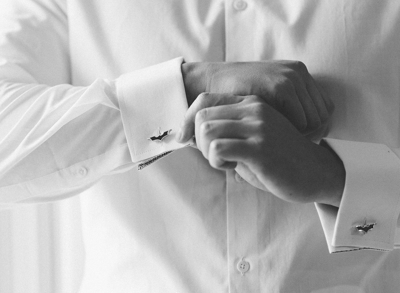 groom getting ready with batman cufflinks