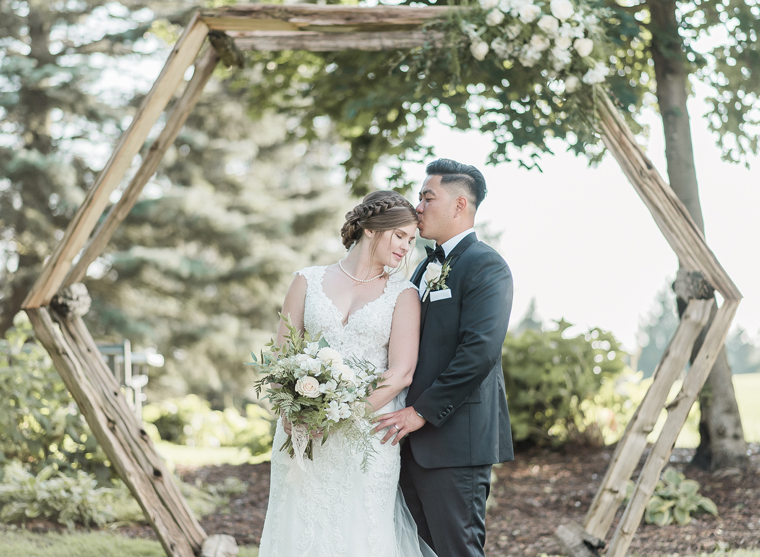bride and groom kissing under wedding ceremony alter